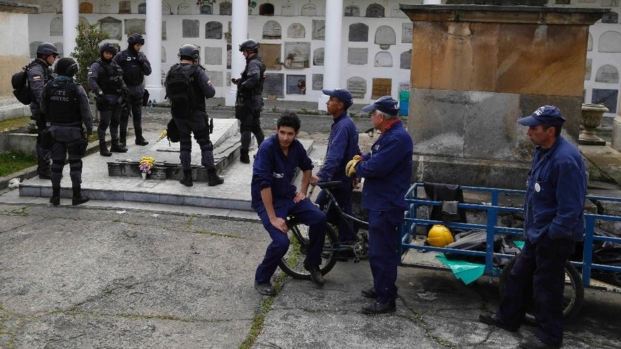 Police officers look at the grave of former M-19 leader Carlos Pizarro as workers prepare to dig up his remains at the central cemetery in Bogota, Colombia, Wednesday, Nov. 26, 2014. Authorities want to perform ballistic tests on the remains of Pizarro, who was killed aboard a commercial plane in mid-flight while running for the presidency in 1990, to revise the still unsolved crime. (AP Photo/Fernando Vergara)
