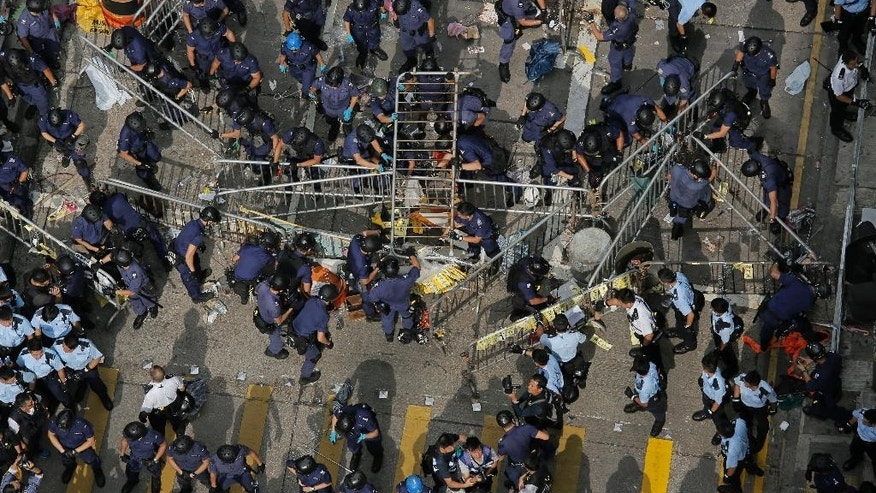 Police officers clear a metal barricades while others tear down tents and canopies and carry away other obstructions after bailiffs issued a warning to the crowd that they would start enforcing the court-ordered clearance at an occupied area in Mong Kok district of Hong Kong Wednesday, Nov. 26, 2014. Hong Kong authorities cleared street barricades from the pro-democracy protest camp in the volatile Mong Kok district for a second day Wednesday after a night of clashes in which police arrested 116 people. (AP Photo/Vincent Yu)