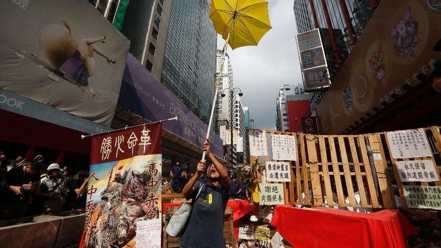 "A protester holds a yellow umbrella, the symbol of Hong Kong's pro-democracy movement, at the barricades as the police keep clearing them away at an occupied area in Mong Kok district of Hong Kong Wednesday, Nov. 26, 2014. Hong Kong authorities cleared street barricades from the pro-democracy protest camp in the volatile Mong Kok district for a second day Wednesday after a night of clashes in which police arrested 116 people. The banner at left reads: ""Revolution should be accomplished."" AP Photo/Kin Cheung)"