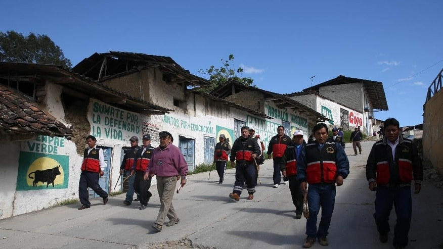"In this June 1, 2014 photo, members of a vigilante group known as ""rondas urbanas,"" or urban patrols, armed with whips, walk through the streets of Cajamarca, Peru. In response to an eroding criminal justice system, self-appointed bands of citizen vigilantes have taken on the work of police, prosecutors and judges. The rise of these citizen enforcers, who enjoy widespread support in Cajamarca, is just one response in Latin America to the failure of police forces to offer the most basic protections. (AP Photo/Martin Mejia)"
