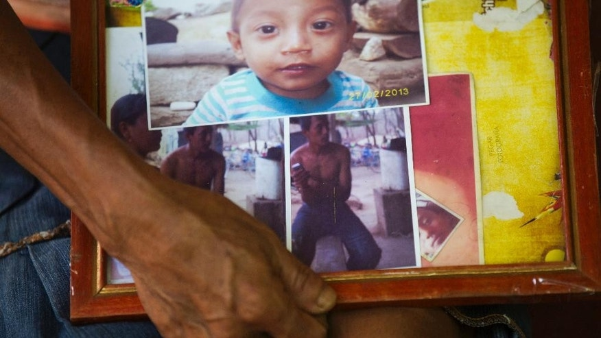 In this May 27, 2014, photo, Odilia Sintu holds a frame with photos of her late son Jose Miguel Ramirez, below, and other relatives at her home in Zacapa, Guatemala. Ramirez went hunting for iguanas on a melon farm, and paid for it with his life. What happened to Ramirez remains in dispute, though no one is pushing for answers any longer. The private security guards alleged to have killed the 19-year-old were never prosecuted. A witness who said he saw the shooting recanted. In a country that averages some 100 homicides a week, the killing barely drew headlines and public attention moved on. (AP Photo/Moises Castillo)