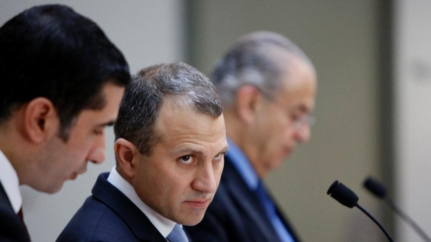 Minister of Foreign Affairs of Lebanon, Gebran Bassil, center, listens to the translator as his Cyprus counterpart Ioannis Kasoulides speaks during a press conference at the foreign ministry house in Capital Nicosia, Wednesday, Nov. 26,  2014. Bassil is in Cyprus for an official visit. (AP Photo/Petros Karadjias)