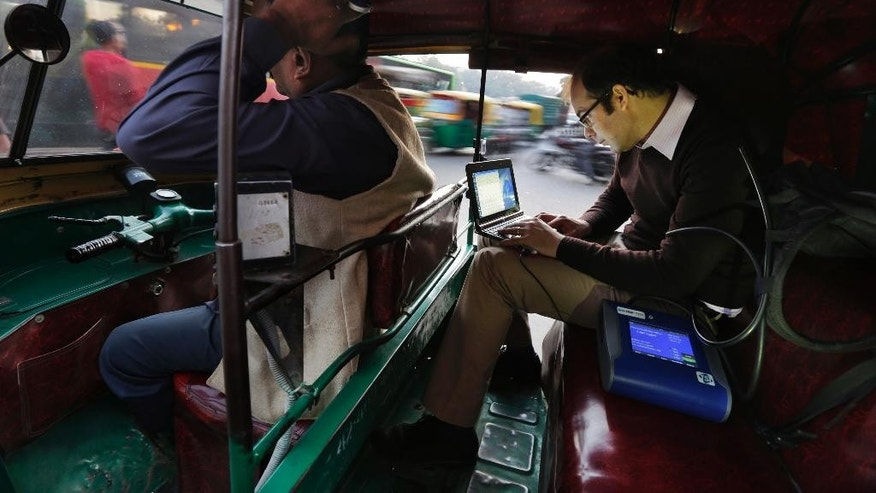 In this Tuesday, Nov. 25, 2014 photo, U.S. scientist Joshua Apte, right, monitors pollution levels on his laptop as he travels in an open-aired auto-rickshaw during rush-hour traffic in New Delhi, India. Apte has alarming findings for anyone who spends time on or near the roads in this city of 25 million, with numbers far worse than the ones that have already led the World Health Organization to rank New Delhi as the world's most polluted city. Average pollution levels, depending on the pollutant, were 50 percent to 8 times higher on the road than urban background readings, including official ambient air pollution measures, according to research by Apte and his partners at the University of California, Berkeley, and the Indian Institute of Technology in New Delhi. (AP Photo/Altaf Qadri)