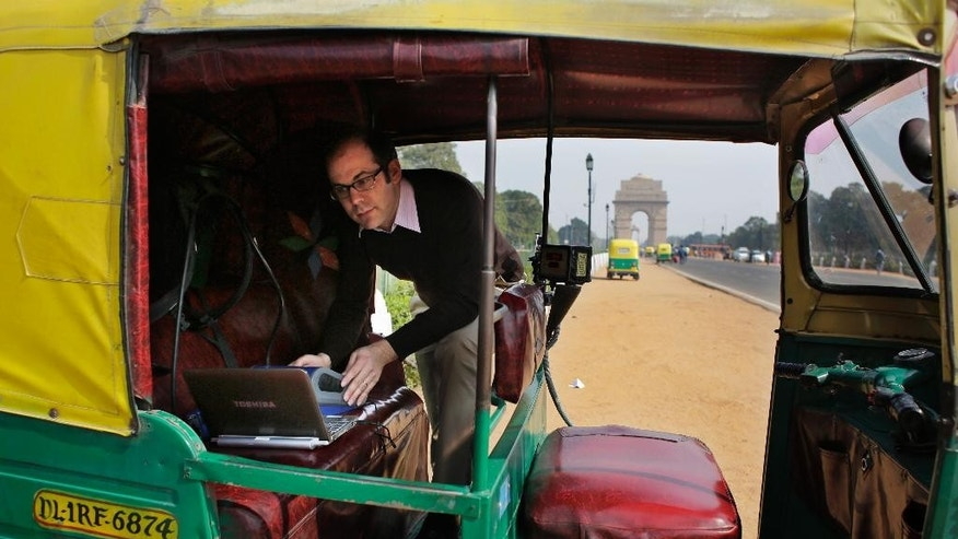 In this Tuesday, Nov. 25, 2014 photo, U.S. scientist Joshua Apte installs air pollution monitoring equipment in an open-aired auto-rickshaw as he prepares to take a ride from the landmark India Gate city center to a southeast suburb to test pollution level during rush-hour traffic in New Delhi, India. Apte has alarming findings for anyone who spends time on or near the roads in this city of 25 million, with numbers far worse than the ones that have already led the World Health Organization to rank New Delhi as the world's most polluted city. Average pollution levels, depending on the pollutant, were 50 percent to 8 times higher on the road than urban background readings, including official ambient air pollution measures, according to research by Apte and his partners at the University of California, Berkeley, and the Indian Institute of Technology in New Delhi. (AP Photo/Altaf Qadri)