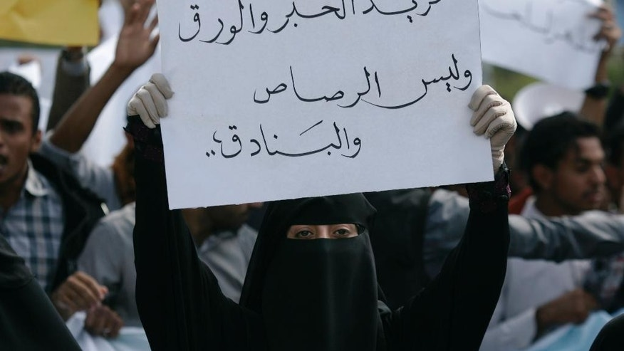 "A student holds a banner with Arabic that reads, ""we want ink and pens not bullets and rifles,"" to protest against the Shiite insurgency during a rally at the University of Sanaa, Yemen, Tuesday, Nov. 25, 2014. (AP Photo/Hani Mohammed)"