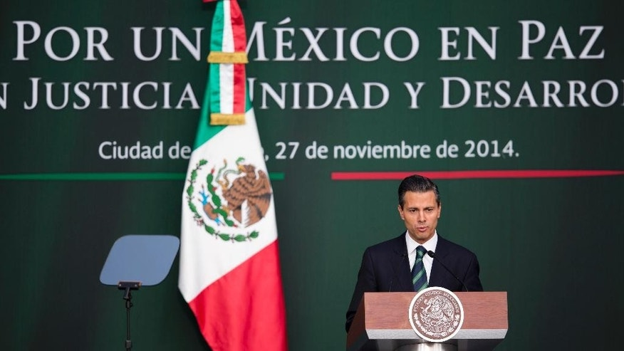 Mexico's President Enrique Pena Nieto speaks during a ceremony at the National Palace in Mexico City, Thursday, Nov. 27, 2014. Mexico's president announced a new anti-crime plan that includes proposals for a nationwide ID, giving Congress the power to dissolve corrupt municipal government and fold their often-corrupt local police forces under the control of the country's 31 state governments. The plan would focus first on four of Mexico's most troubled states, Guerrero, Michoacan, Jalisco and Tamaulipas. (AP Photo/Eduardo Verdugo)