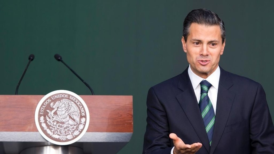 Mexico's President Enrique Pena Nieto gestures after addressing the audience during a ceremony at the National Palace in Mexico City, Thursday, Nov. 27, 2014. Mexico's president announced a new anti-crime plan that includes proposals for a nationwide ID, giving Congress the power to dissolve corrupt municipal government and fold their often-corrupt local police forces under the control of the country's 31 state governments. The plan would also streamline the complex divisions between federal, state and local offenses. At present, some local police refuse to act to prevent federal crimes like drug trafficking.  The plan would focus first on four of Mexico's most troubled states, Guerrero, Michoacan, Jalisco and Tamaulipas. It would also send more federal police and other forces to those states. (AP Photo/Eduardo Verdugo)