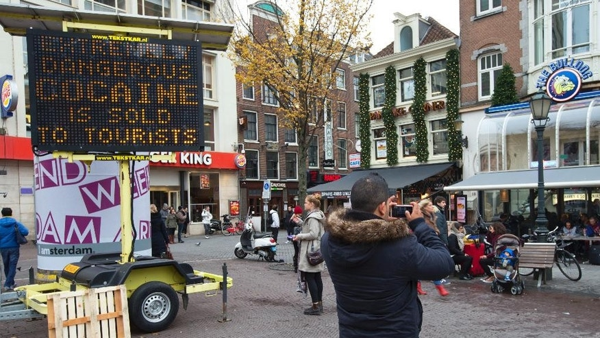 A man takes a picture of Amsterdam's famous Bulldog coffeeshop where hashish and marijuana are legally sold as an electronic sign warns tourists of extremely dangerous cocaine being sold to tourist on Leiseplein square in the center of Amsterdam, Netherlands, Thursday, Nov. 27, 2014. Health authorities in Amsterdam are warning of dangerous drugs being sold to tourists after three British men died in the last month after snorting heroin they may have believed was cocaine. (AP Photo/Peter Dejong)