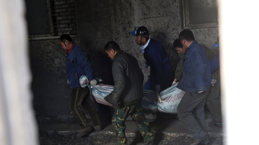 Nov. 26, 2014: rescuers carry the body of a victim from Hengda coal mine run by the state-owned Fuxin Coal Corp. in Fuxin, Liaoning province, China.