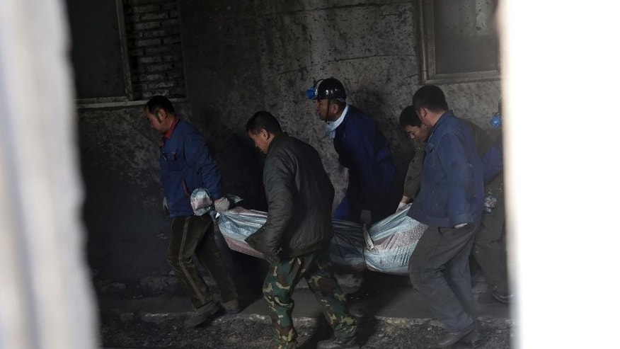 In this Wednesday, Nov. 26, 2014 photo, rescuers carry the body of a victim from Hengda coal mine run by the state-owned Fuxin Coal Corp. in Fuxin, Liaoning province, China. At least 11 people were killed Thursday, Nov. 27 in the second deadly coal mine accident to hit China in two days, pointing to continuing safety issues in the industry despite a major decline in deaths among miners in recent years. Thursday's blast follows an explosion and fire early Wednesday morning in the northeastern province of Liaoning in which 26 miners were killed. (AP Photo/Xinhua, Li Gang) NO SALES