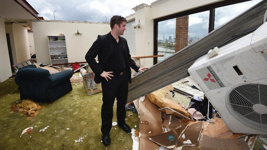 James Marriott surveys the damage in his roofless apartment, Friday, Nov. 28, 2014, in the inner city suburb of Toowong in Brisbane, Australia, after a severe thunderstorm swept through the city Thursday. Australia's third-largest city, was lashed by its worst storm in decades, with wind, rain and hail lifting roofs, cutting power lines, flooding streets and injuring a dozen people, officials said. (AP Photo/AAP Image, Dan Peled) AUSTRALIA OUT, NEW ZEALAND OUT, PAPUA NEW GUINEA OUT, SOUTH PACIFIC OUT, NO SALES
