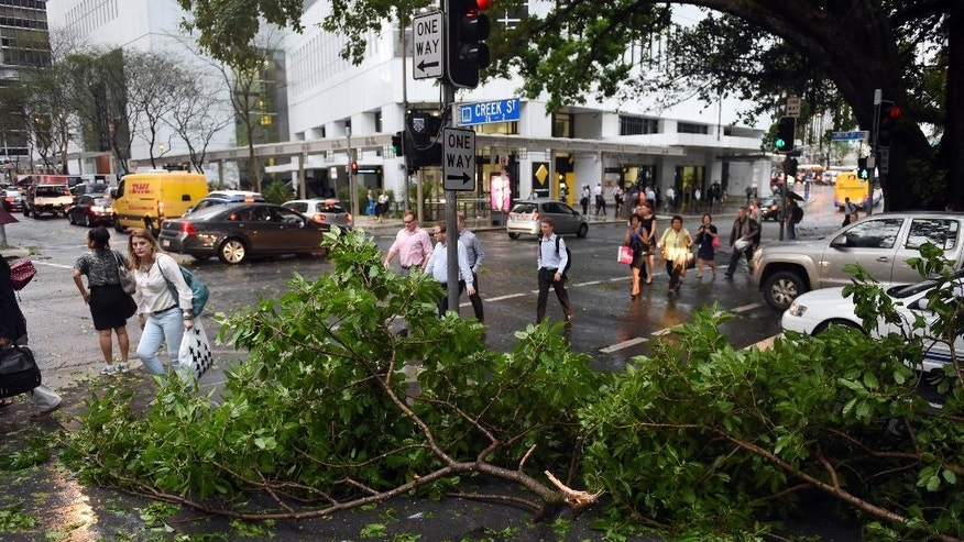 In this Thursday, Nov. 27, 2014 photo, people walk past fallen tree branches in Brisbane, Australia, after a severe thunderstorm swept through the city. Australia's third-largest city, was lashed by its worst storm in decades, with wind, rain and hail lifting roofs, cutting power lines, flooding streets and injuring a dozen people, officials said. (AP Photo/AAP Image, Dan Peled) AUSTRALIA OUT, NEW ZEALAND OUT, PAPUA NEW GUINEA OUT, SOUTH PACIFIC OUT, NO SALES