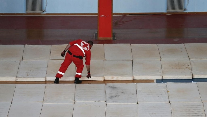 A Greek Red Cross volunteer lays out mattresses inside an indoor basketball stadium where authorities plan to temporarily host some 700 migrants on a crippled freighter being towed to the southern Cretan port town of Ierapetra, Greece, on Wednesday, Nov. 26, 2014. Hampered by gale-force winds, a Greek navy frigate was expected to arrive in Ierapetra late Wednesday with the migrants, believed to include refugees from Syria and Afghanistan. (AP Photo/Petros Giannakouris)