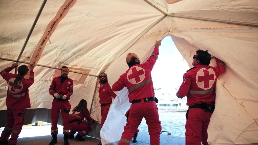 Greek Red Cross volunteers set up a tent which will be used to receive and offer initial care to hundreds of immigrants on a crippled freighter being towed to the southern Cretan port town of Ierapetra, Greece, on Wednesday, Nov. 26, 2014. Hampered by gale-force winds, a Greek navy frigate was expected to arrive in Ierapetra late Wednesday with the estimated 700 migrants, believed to include refugees from Syria and Afghanistan. (AP Photo/Petros Giannakouris)