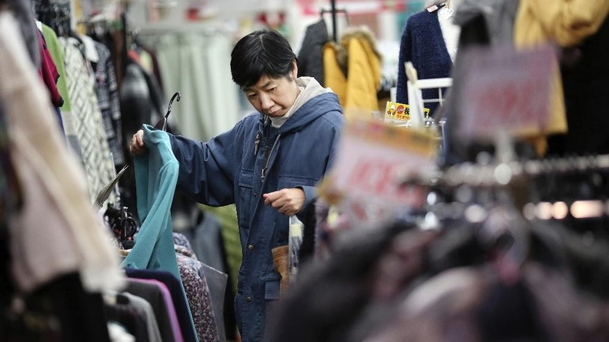 In this Nov. 20, 2014 photo, a woman looks at clothing at a shop in Sugamo, where known as a shopping street for the older generation, in Tokyo. Japan's inflation rate fell to a six-month low, highlighting the difficulty Prime Minister Shinzo Abe faces in his campaign to overcome deflation in the world's third-largest economy. The core consumer price index, excluding fresh foods, rose 2.9 percent in October from a year earlier, according to data released Friday, Nov. 28, 2014. (AP Photo/Eugene Hoshiko)