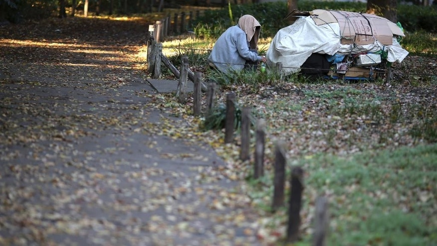 In this Nov. 27, 2014 photo, a homeless man sits in a park in Tokyo. Japan's inflation rate fell to a six-month low, highlighting the difficulty Prime Minister Shinzo Abe faces in his campaign to overcome deflation in the world's third-largest economy. The unemployment rate eased slightly, according to data released Friday, Nov. 28. (AP Photo/Eugene Hoshiko)