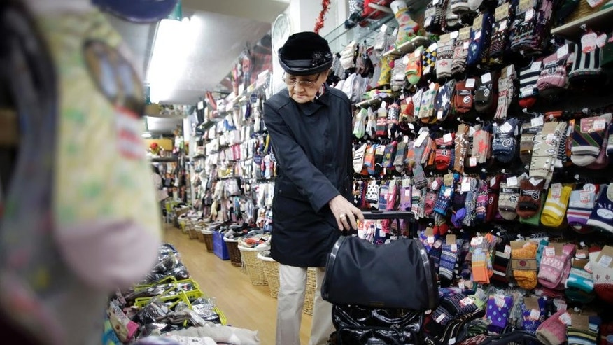 In this Nov. 20, 2014 photo, a woman looks at socks at a shop in Sugamo, where known as a shopping street for the older generation, in Tokyo.  Japan's inflation rate fell to a six-month low, highlighting the difficulty Prime Minister Shinzo Abe faces in his campaign to overcome deflation in the world's third-largest economy. The core consumer price index, excluding fresh foods, rose 2.9 percent in October from a year earlier, according to data released Friday, Nov. 28, 2014. (AP Photo/Eugene Hoshiko)