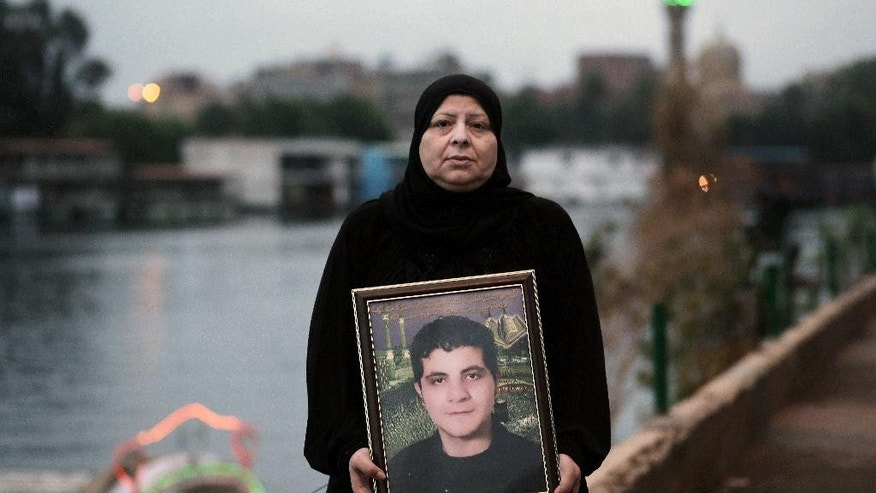 "In this Tuesday, Nov. 25, 2014 photo, Amel Shaker holds a portrait of her 25-year-old son Ahmed, who was fatally shot in the back on the ""Friday of Rage,"" one of the bloodiest days of Egypt's 2011 uprising against longtime autocrat Hosni Mubarak, in Cairo, Egypt. A verdict is expected on Saturday in Mubarak's trial on charges connected to the killings of more than 900 protesters against his rule. But what was originally billed as Egypt's ""trial of the century"" has largely faded from public attention after a drawn-out trial and re-trial and after upheaval that has flipped the political narrative. (AP Photo/Nariman El-Mofty)"
