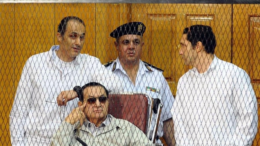"FILE - In this Saturday, Sept. 14, 2013 file photo, former Egyptian President Hosni Mubarak, seated, and his two sons Gamal Mubarak, left, and Alaa Mubarak, right, attend a hearing in a courtroom at the Police Academy, Cairo, Egypt. A verdict is expected on Saturday in Mubarak's trial on charges connected to the killings of more than 900 protesters against his rule. But what was originally billed as Egypt's ""trial of the century"" has largely faded from public attention after a drawn-out trial and re-trial and after upheaval that has flipped the political narrative. (AP Photo/Ahmed Omar, File)"