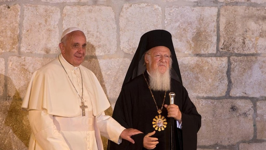 FILE - In this May 25, 2014 file photo, Pope Francis stands with Ecumenical Patriarch Bartholomew I as they meet outside the Church of the Holy Sepulchre, in Jerusalem's Old City. Pope Francis travels to Turkey on a three day visit beginning Friday Nov. 28, 2014, amid new Muslim-Christian tensions and a violent war next door, with Islamic State militants seizing chunks of territory in Iraq and Syria and sending 1.6 million refugees across the border into Turkey. Francis is due to visit the spiritual leader of the world's Orthodox Christians, Patriarch Bartholomew I. (AP Photo/Sebastian Scheiner, File)
