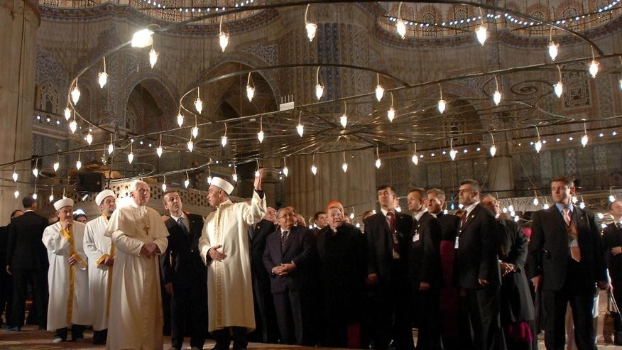 "FILE -  In this Nov. 30, 2006 file photo Pope Benedict XVI, third left, and Mufti of Istanbul Mustafa Cagrici, fifth left, visit the Sultanahmet Mosque, known as Blue Mosque, in Istanbul, Turkey. Pope Francis travels to Turkey on a three day visit beginning Friday Nov. 28, 2014, amid new Muslim-Christian tensions and a violent war next door, with Islamic State militants seizing chunks of territory in Iraq and Syria and sending 1.6 million refugees across the border into Turkey. Asked if Francis would pray in the mosque as Benedict did, Vatican spokesman father Federico Lombardi took pains to stress the difference between a formal, ritualistic prayer that a Catholic might recite in church and a respectful ""spiritual meditation"" in a place of worship of another faith. (AP Photo/Salih Zeki Fazlioglu/Anatolia) TURKEY OUT, EDITORIAL USE ONLY"