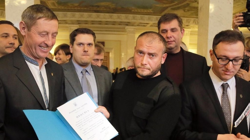 A newly elected Ukrainian parliament lawmaker, and Right Sector leader Dmytro Yarosh, center, surrounded by lawmakers  shows the text of his oath during the opening  first session in Kiev, Ukraine, Thursday, Nov. 27, 2014. The Parliament in Ukraine has opened for its first session since an election last month that ushered in a spate of pro-Western parties. (AP Photo/Efrem Lukatsky)