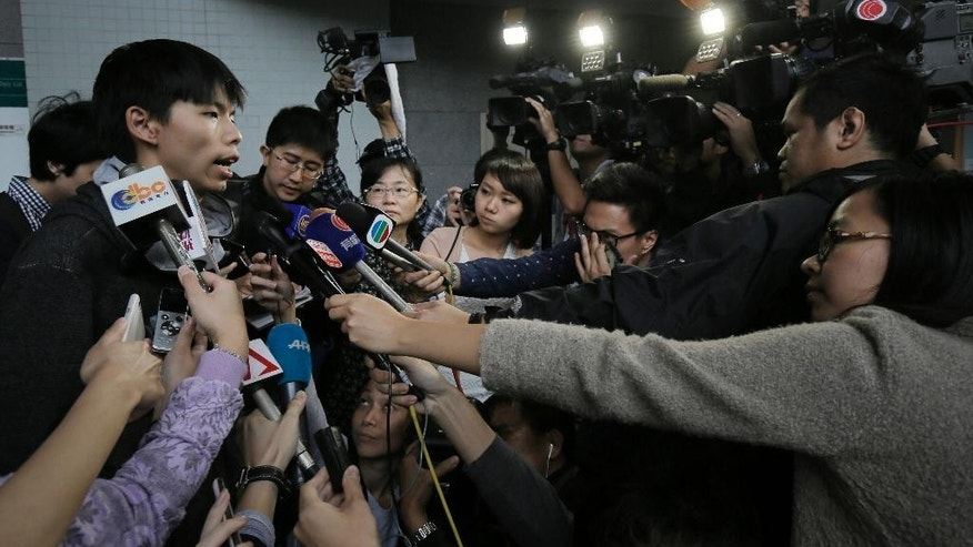 Prominent Hong Kong student protest leader Joshua Wong, left, talks to reporters outside a court in Hong Kong Thursday, Nov. 27, 2014. Wong and other democracy protesters were arrested during a police operation to remove barricades from a protest camp in the unruly Mong Kok district. Wong was given bail and his case adjourned until January 14. (AP Photo/Vincent Yu)
