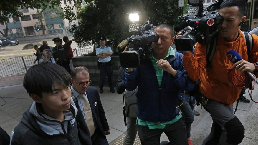 Prominent Hong Kong student protest leader Joshua Wong, left, walks out from a court with his lawyer in Hong Kong Thursday, Nov. 27, 2014. Wong and other democracy protesters were arrested the day before during a police operation to remove barricades from a protest camp in the unruly Mong Kok district. Wong was given bail and his case adjourned until January 14. (AP Photo/Vincent Yu)