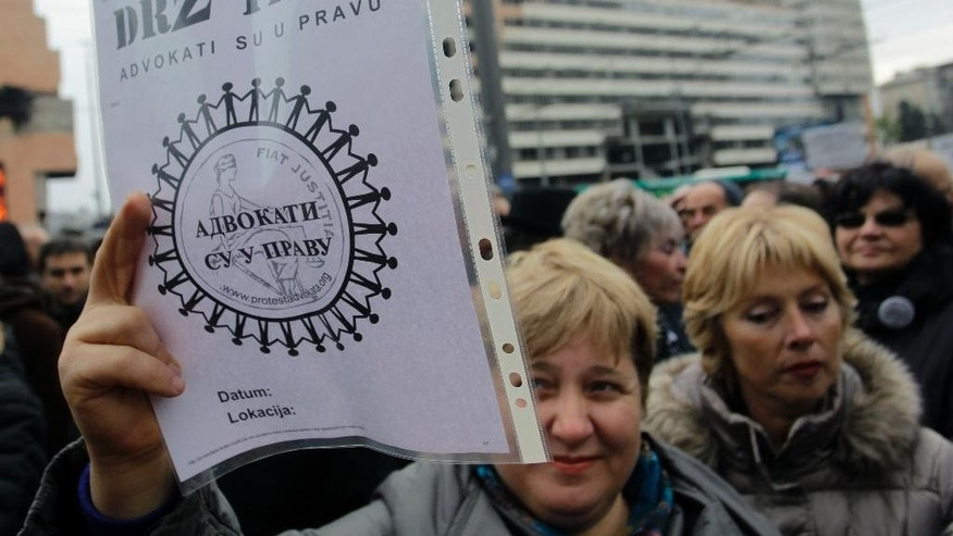 "A lawyer holds a sheet of  paper that reads ""Hang In There, The Lawyers Are Right"" during the protest in front of the government headquarters, in Belgrade, Serbia, Thursday, Nov. 27, 2014. Serbia's striking lawyers have asked for EU help to resolve a three-month old dispute with the government that has practically paralyzed the judiciary in the Balkan country seeking to join the bloc. (AP Photo/Andrej Cukic)"