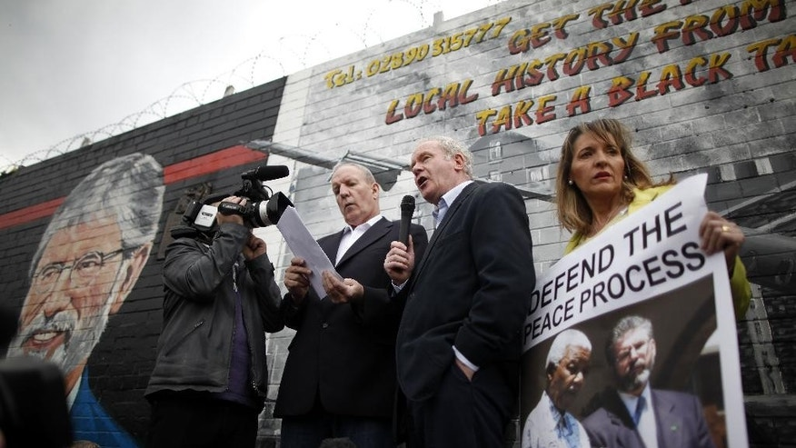 FILE - A Saturday, May 3, 2014 photo from files showing Sinn Fein's Martin McGuinness, centre, with party members Bobby Storey, left, and Martina Anderson speaking during a protest rally on the Falls Road, West Belfast, Northern Ireland. A prominent Irish Republican Army veteran has been arrested on suspicion of involvement in the IRA's 1972 abduction, killing and secret burial of a widowed mother of 10, one of the outlawed group's most notorious slayings. The Irish nationalist Sinn Fein party says its Northern Ireland chairman, Bobby Storey, was arrested Wednesday, Nov. 26, 2014. Police say he's being interrogated about the killing of 38-year-old Jean McConville, whose remains were found bear an Irish beach in 2003. (AP Photo/Peter Morrison, File)