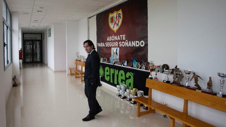 Rayo Vallecano club president Raul Martin Presa walks past some trophies after leaving a news conference in Madrid, Spain, Thursday, Nov. 27, 2014. Spanish first division soccer team Rayo Vallecano says it has opened a bank account for donations for Carmen Martinez, an 85-year-old woman whose eviction last week sparked an outcry.  Martinez was evicted from the apartment she owned and lived in for decades in Madrid's working class neighborhood of Vallecas. Her son had used it as collateral for a euro40,000  loan ($50,000) and could not make payments after losing his job. Associated Press photos of the eviction spurred intense Spanish media coverage of Martinez' plight and prompted the club to help her. Rayo is also from the Vallecas neighborhood. (AP Photo/Paul White)