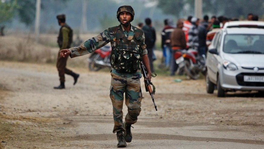 An Indian Army soldier gives orders to his colleagues during exchange of gunfire with armed suspected militants at Pindi Khattar village in Arnia border sector, 43 kilometers (27 miles) south of Jammu, India, Thursday, Nov. 27, 2014. An army officer says some of the militants occupied an abandoned bunker in Jammu region early Thursday and fired at the soldiers in Arnia sector in the Indian portion of Kashmir. (AP Photo/Channi Anand)