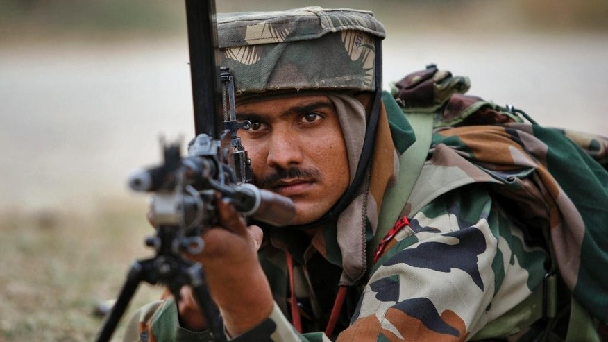 An Indian Army soldier takes position during an encounter with armed suspected militants at Pindi Khattar village in Arnia border sector, 43 kilometers (27 miles) south of Jammu, India, Thursday, Nov. 27, 2014. An army officer says some of the militants occupied an abandoned bunker in Jammu region early Thursday and fired at the soldiers in Arnia sector in the Indian portion of Kashmir. (AP Photo/Channi Anand)