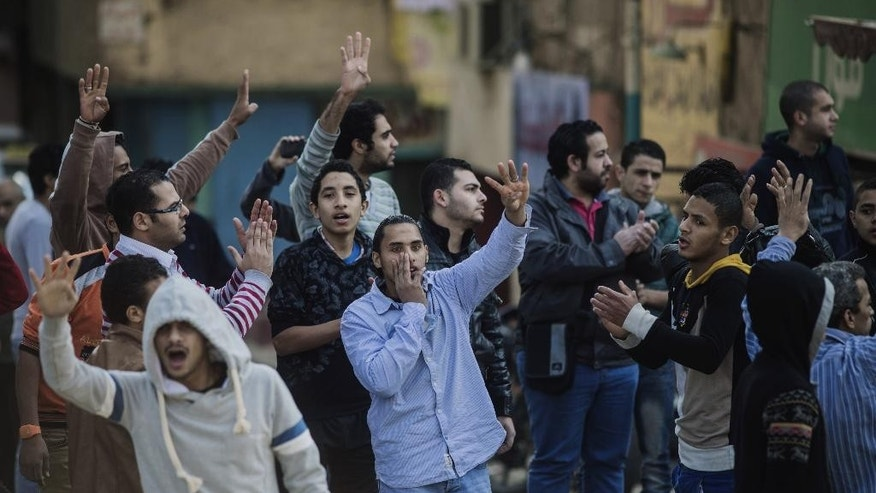People raise the four-finger sign symbolizing the sit-in at a mosque where hundreds were killed by the Egyptian military in August 2013, as they protest against the Egyptian government on Al Haram Street in Giza, a neighboring city of Cairo, Egypt, Friday, Nov. 28, 2014. At least two senior Egyptian army officers were killed early Friday morning as security forces arrested more than 100 Islamists ahead of planned anti-government demonstrations. (AP Photo/Eman Helal)