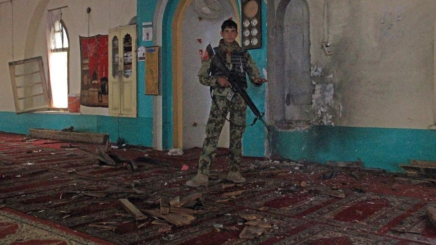 An Afghan soldier stands guard inside a mosque after a bomb explosion in khogyani district of Nangarhar province east of Kabul, Afghanistan, Friday, Nov. 28, 2014. An Afghan official says six Afghan soldiers have been killed in an attack on a military base in the southern Helmand province that lasted more than 14 hours. In Nangahar province, an official says 31 people were wounded when a mosque was bombed during Friday prayers. (AP Photo)