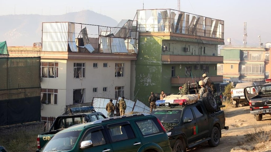Afghan security forces inspect the site of an attack in Kabul, Afghanistan, Friday, Nov. 28, 2014. Taliban fighters staged an attack Thursday evening in an upscale district in the Afghan capital Kabul. Witnesses described multiple explosions and bursts of gunfire in the Wazir Akbar Khan district, which contains numerous foreign embassies and compounds housing international agencies and companies - as well as the homes of some senior Afghan government officials. (AP Photo/Rahmat Gul)