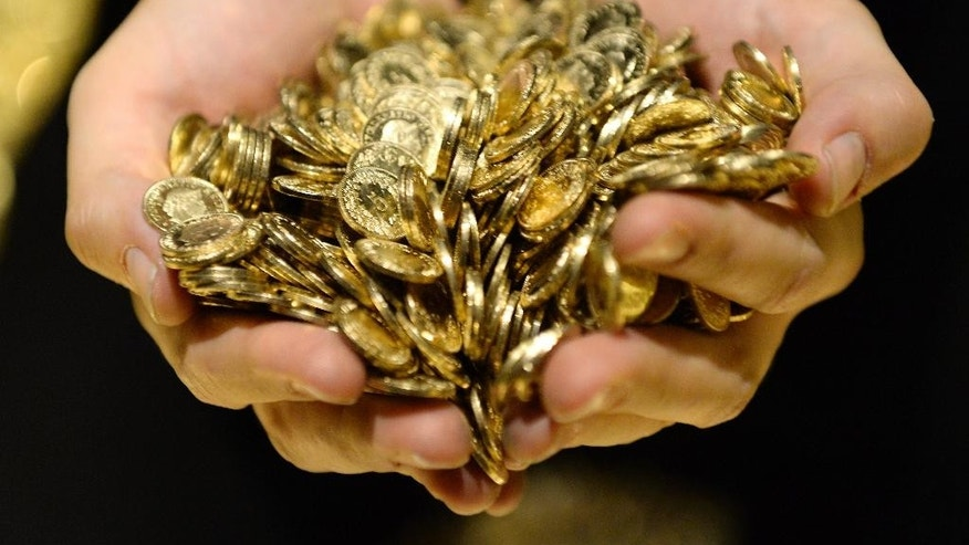 FILE - in this Nov. 16, 2014 file photo a person holds gold coins during an exhibition in Lenzburg, Switzerland. In Switzerland, a campaign is on to protect the country's wealth by investing in gold  a lot of gold. In a test of their sense of financial security, the Swiss are being asked to vote on a proposal to make the central bank hold a fifth of its reserves in gold within five years. That would mean buying 1,500 metric tons, or 1,650 short tons, of gold worth more than US$60 billion. (AP Photo/Keystone, Steffen Schmidt) EDITORIAL USE ONLY, NO SALES, NO ARCHIVES