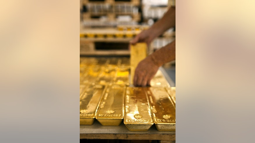 FILE - In this Aug. 8, 2011 file photo a person takes a gold bar in the gold store of the Cantonal Bank of Zurich ZKB in Zurich, Switzerland.  In Switzerland, a campaign is on to protect the country's wealth by investing in gold _ a lot of gold. In a test of their sense of financial security, the Swiss are being asked to vote on a proposal to make the central bank hold a fifth of its reserves in gold within five years. That would mean buying 1,500 metric tons, or 1,650 short tons, of gold worth more than US$60 billion. (AP Photo/Keystone, Martin Ruetschi) EDITORIAL USE ONLY, NO SALES, NO ARCHIVES