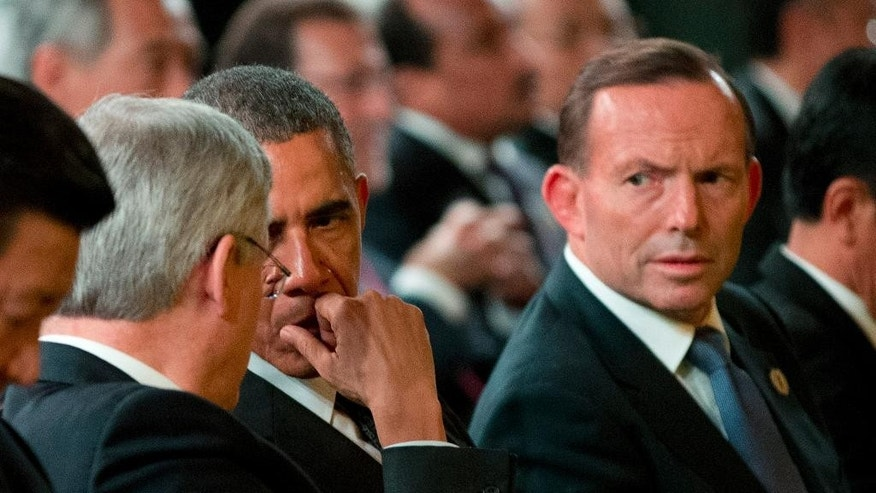 FILE - In this Nov. 15, 2014 file photo, Australian Prime Minister Tony Abbott, right, looks on as U.S. President Barack Obama, third left, and Canadian Prime Minister Stephen Harper, second left, talk prior to the start of the Welcome to Country ceremony by Aboriginal and Torres Strait Island people at the G-20 summit in Brisbane, Australia. Abbott, who rose to power in large part by opposing a tax on greenhouse gas emissions, is finding his country isolated like never before on climate change as the U.S., China and other nations signal new momentum for action. (AP Photo/Mark Baker, File)
