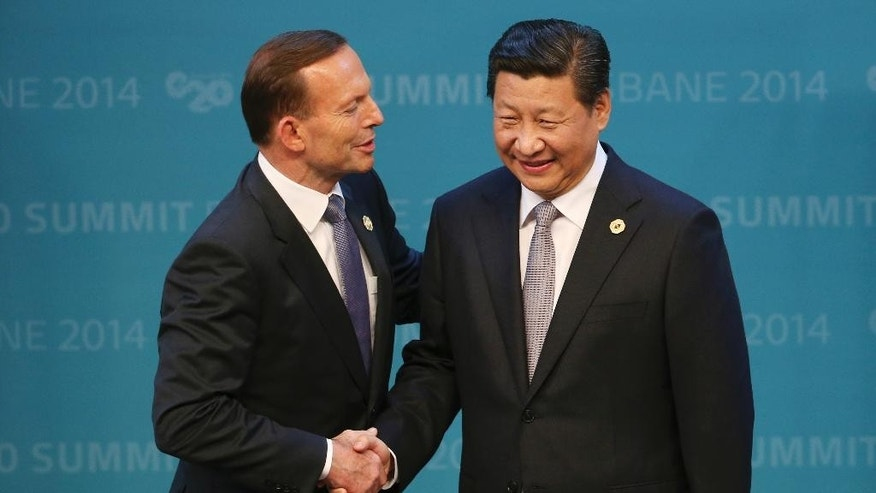In this Nov. 15, 2014 photo, Australian Prime Minister Tony Abbott, left, welcomes Chinese President Xi Jinping to the G-20 summit in Brisbane, Australia. Abbott, who rose to power in large part by opposing a tax on greenhouse gas emissions, is finding his country isolated like never before on climate change as the U.S., China and other nations signal new momentum for action. (AP Photo/Rob Griffith)