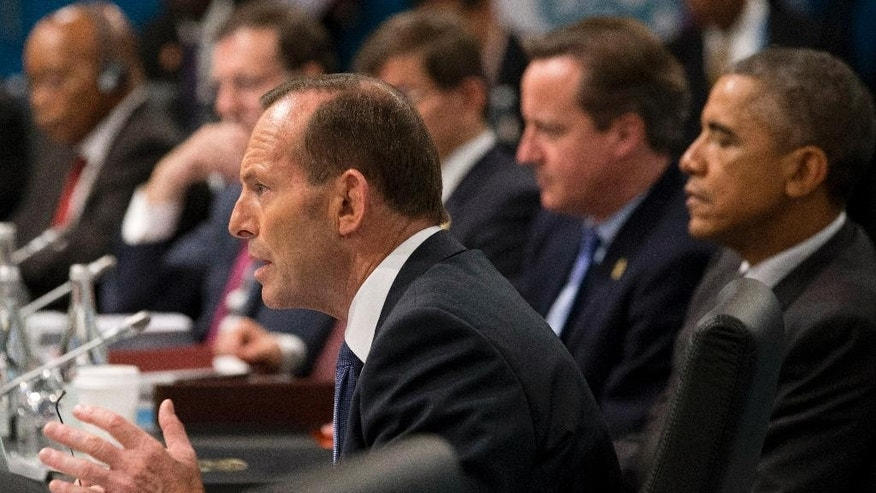 In this Nov 15, 2014 photo, Australian Prime Minister Tony Abbott addresses leaders including U.S. President Barack Obama, right, and British Prime Minister David Cameron, second right, during a plenary session of the G-20 summit in Brisbane, Australia. Abbott, who rose to power in large part by opposing a tax on greenhouse gas emissions, is finding his country isolated like never before on climate change as the U.S., China and other nations signal new momentum for action. (AP Photo/Rob Griffith, Pool)