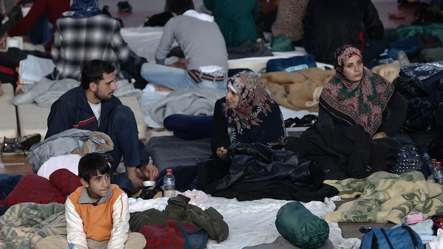 Immigrants who arrived on a cargo ship from Turkey sit on their bedding on the floor of a basketball arena where they have been given temporary shelter in the town of Ierapetra, on the southern Greek island of Crete on Friday, Nov. 28, 2014. Nearly 600 men, women and children, mostly refugees from Syria, have been temporarily put up in the southern Cretan town of Ierapetra, where they arrived in a crippled smuggling ship after more than a week at sea. (AP Photo/Petros Giannakouris)
