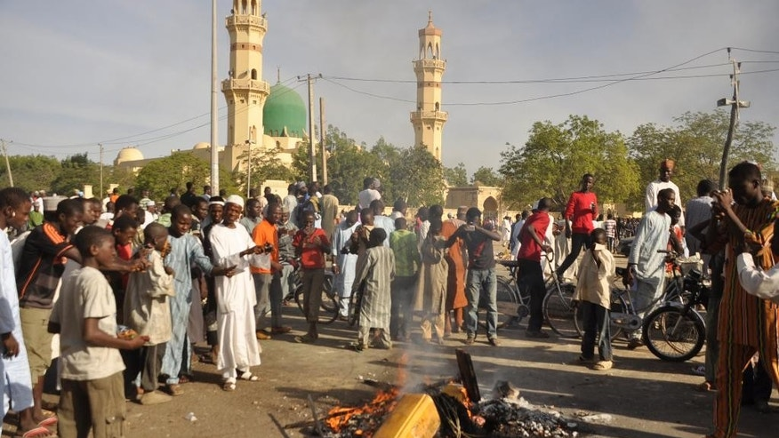 People gather at the site of a bomb explosion in Kano, Nigeria, Friday Nov. 28, 2014. An explosion tore through the central mosque in Nigeria's second-largest city on Friday, and officials feared the casualty toll would be high. Capt. Ikechukwu Eze said the Friday blast occurred at the main mosque in the city of Kano. Hundreds had gathered to listen to a sermon in a region terrorized by attacks from the militant group Boko Haram. (AP Photo/Muhammed Giginyu)