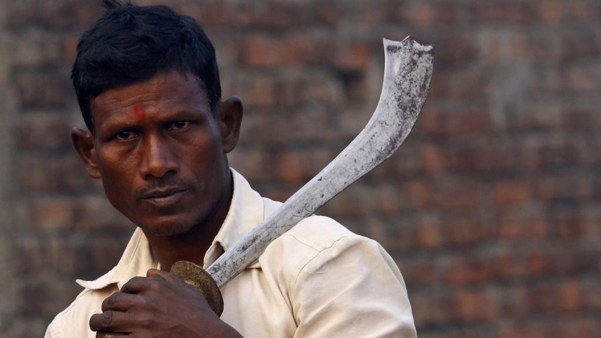 A butcher with a butcher knife stand to participate in a mass sacrifice ceremony at Gadhimai temple in the jungles of Bara district, about 160 miles (100 miles) south of Katmandu, Nepal, Friday, Nov. 28, 2014. A festival believed to be the largest animal sacrifice ritual in the world began Friday in southern Nepal, where devotees believe the sacrifices bring good luck and a Hindu goddess will grant their wishes. Organizers and the authorities defend the festival held every five years as a generations-old tradition, though animal rights activists decry it as barbaric. During the 2009 festival, an estimated 200,000 animals and birds were sacrificed. (AP Photo/Sunil Sharma)