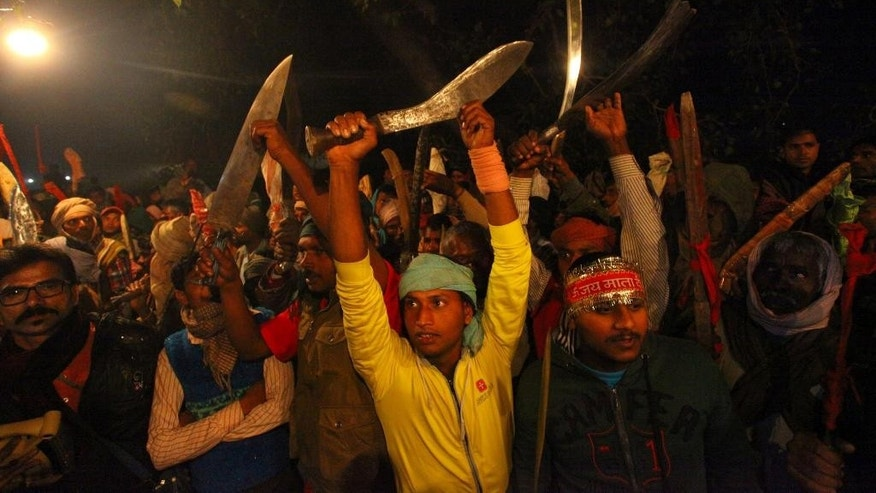 Butchers with butcher knives participate in religious rituals before slaughtering buffalos during a mass sacrifice ceremony at Gadhimai temple in in the jungles of Bara district about 160 miles (100 miles) south of Katmandu, Nepal, Friday, Nov. 28, 2014. A festival believed to be the largest animal sacrifice ritual in the world began Friday in southern Nepal, where devotees believe the sacrifices bring good luck and a Hindu goddess will grant their wishes. Organizers and the authorities defend the festival held every five years as a generations-old tradition, though animal rights activists decry it as barbaric. During the 2009 festival, an estimated 200,000 animals and birds were sacrificed. (AP Photo/Sunil Sharma)