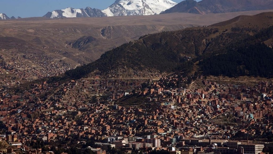 FILE - In this Nov. 14, 2007 file photo, the 6,010-meter Huayna Potosi is seen above La Paz. El Alto and its sister city of La Paz, the world's highest capital, depend on glaciers for at least a third of their water, more than any other urban sprawl. But that supply is in peril. Global warming has doomed the world's tropical glaciers. Negotiators from more than 190 countries will meet Dec. 1, 2014, in the Peruvian capital, for two weeks to work on drafts for a global climate deal that is supposed to be adopted next year in Paris. (AP Photo/Dado Galdieri, File)