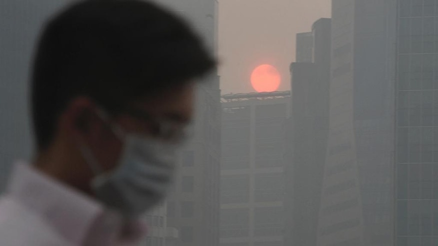 FILE- In this June 20, 2013 file photo, a masked man walks as the sun sets among buildings covered with haze, as Singapore urged people to remain indoors amid unprecedented levels of air pollution, at the Singapore Central Business District. Pledges by Chinese President Xi Jinping and U.S. President Barack Obama in November 2014, to limit their emissions after 2020, sent a powerful signal that a global deal could be possible next year. (AP Photo/Joseph Nair, File)