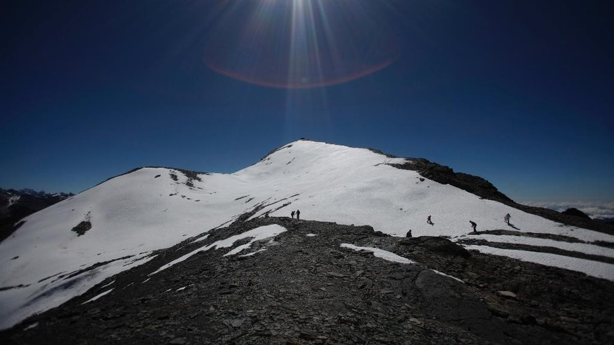 FILE- In this June 12, 2011 file photo, people walk along the Cordillera Real of the Andes mountains on the outskirts of La Paz, Bolivia. According to the Environmental Defense League, a Bolivian NGO, Bolivia's glaciers along the Cordillera Real, Chacaltaya, Tuni Condorini and Illimani are shrinking in size by more than one meter every year and estimate that the majority of the snow in this area could disappear by 2030. A scientific assessment by the U.N.'s expert panel on climate change warned that rising global temperatures could have an irreversible impact on people and ecosystems as glaciers melt, sea levels rise, heat waves intensify and oceans become warmer and more acidic. (AP Photo/Juan Karita)
