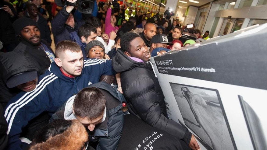 Shoppers jostle for electrical goods at a store in London, Friday Nov. 28, 2014. Americans celebrating Thanksgiving in Britain may have felt right at home as Black Friday shopping chaos caused some disruption. The practice of offering bargain basement prices the day after Thanksgiving has spread across the Atlantic, with some retailers opening overnight to lure determined shoppers. (AP Photo/PA, David Parry) UNITED KINGDOM OUT