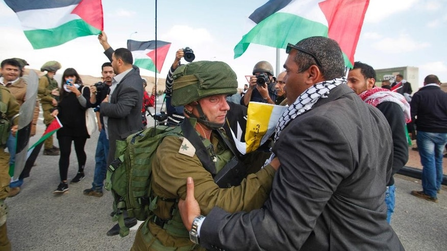 Israeli soldier pushes a  Palestinian protester as they try to block a highway between Jerusalem and the Dead Sea near the West Bank town of Jericho Friday, Nov. 28, 2014. (AP Photo/Nasser Shiyoukhi)